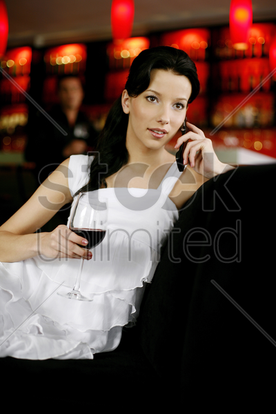 woman holding a glass of red wine while talking on the phone stock photo