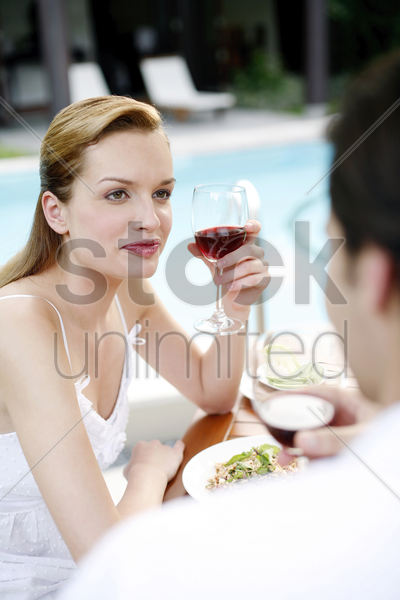 woman holding a glass of red wine while talking to her boyfriend stock photo