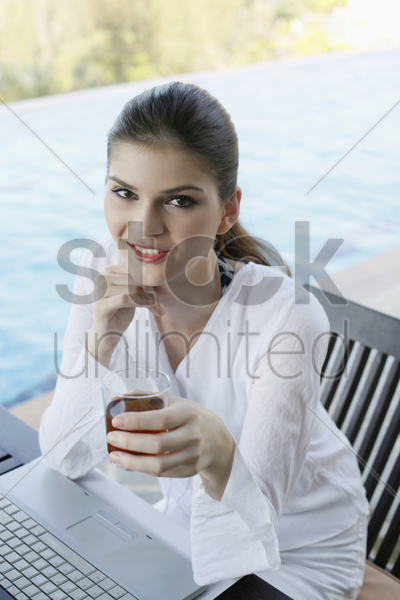 woman holding a glass of tea and smiling stock photo