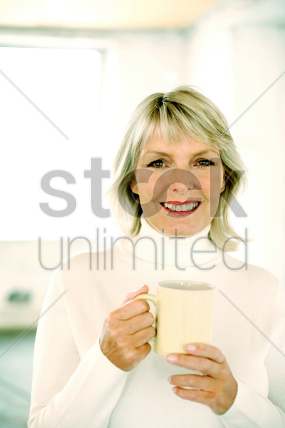 woman holding a glass while smiling at the camera stock photo