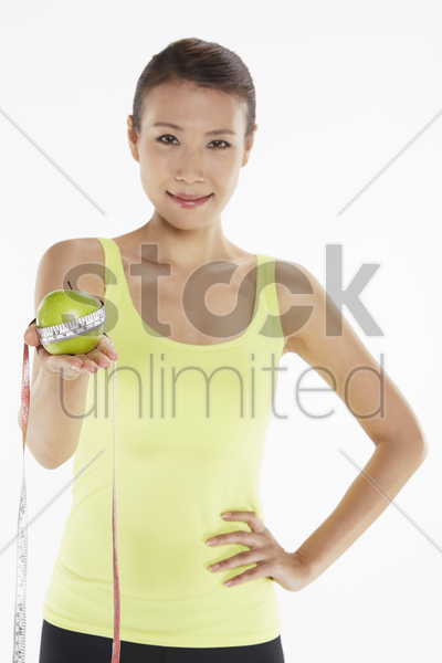 woman holding a green apple and a weight scale stock photo