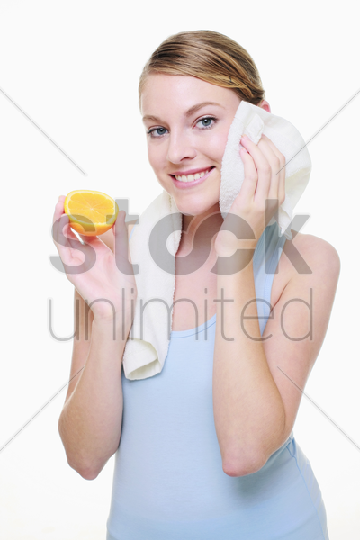 woman holding a halved orange and wiping her sweat with towel stock photo