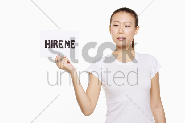 woman holding a 'hire me' sign stock photo