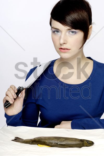 woman holding a knife with fish on the table stock photo
