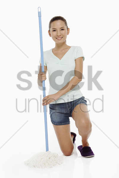 woman holding a mop and smiling stock photo