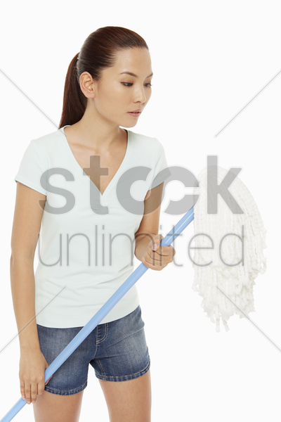 woman holding a mop stock photo