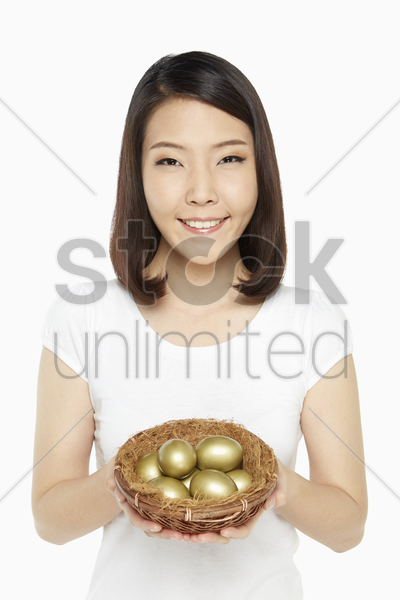 woman holding a nest filled with gold eggs stock photo