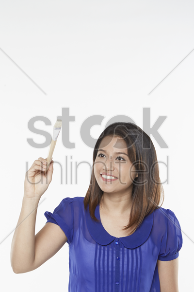 woman holding a paint brush stock photo