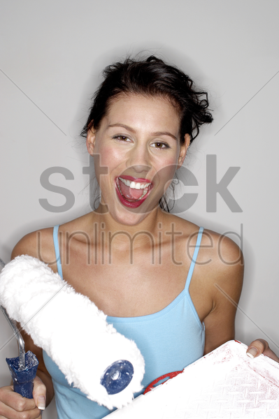 woman holding a paint roller and a paint tray stock photo