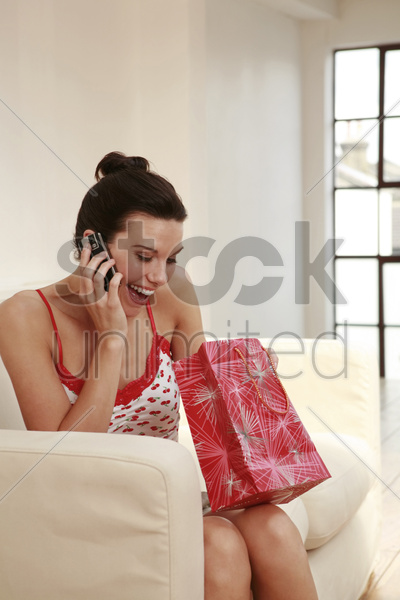 woman holding a paper bag while talking on the mobile phone stock photo