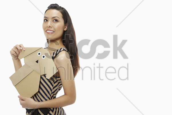 woman holding a paper dog stock photo