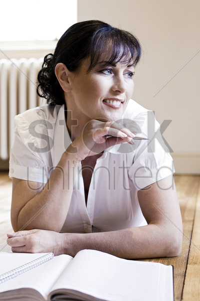 woman holding a pen while thinking stock photo
