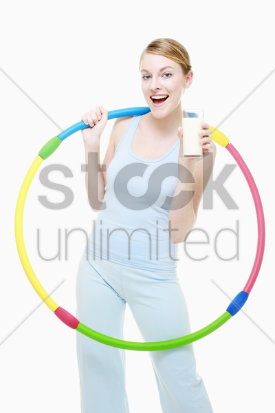 woman holding a plastic hoop and a glass of milk stock photo