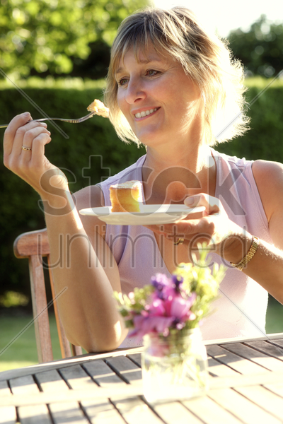 woman holding a plate of cake stock photo