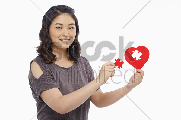 woman holding a puzzle piece from a heart shape stock photo