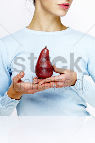woman holding a red pear stock photo