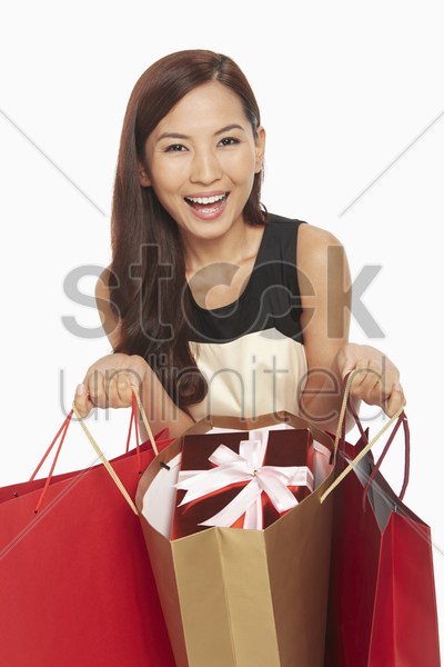 woman holding a shopping bag with gift box inside stock photo
