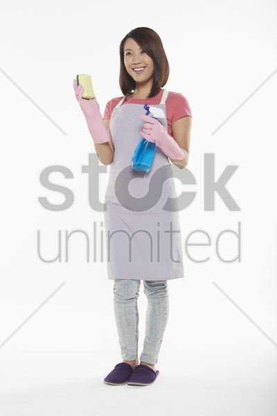 woman holding a sponge and spray bottle stock photo