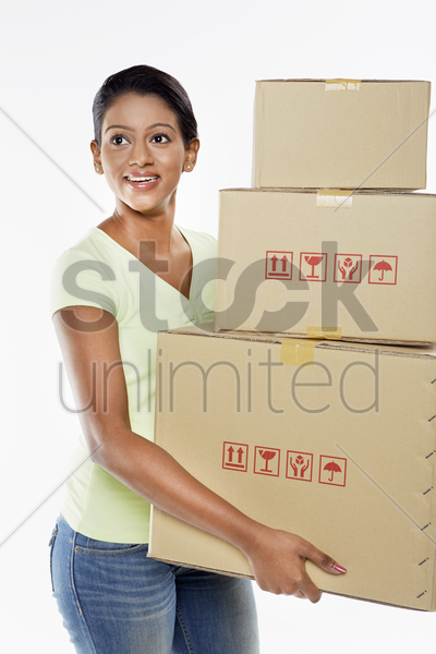 woman holding a stack of cardboard boxes stock photo