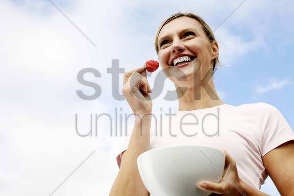 woman holding a strawberry and a bowl stock photo