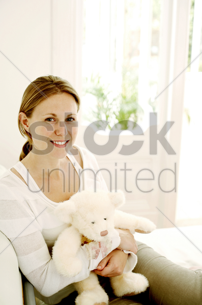 woman holding a teddy bear stock photo