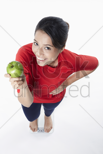woman holding an apple while standing on weighing machine stock photo
