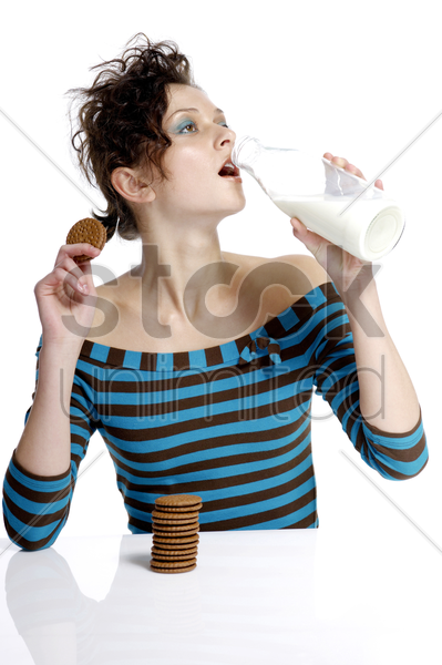 woman holding biscuit while drinking a bottle of milk stock photo