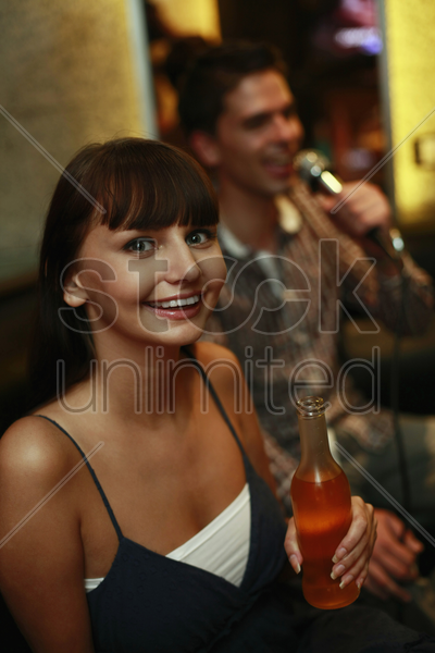 woman holding bottled drink, man singing in the background stock photo