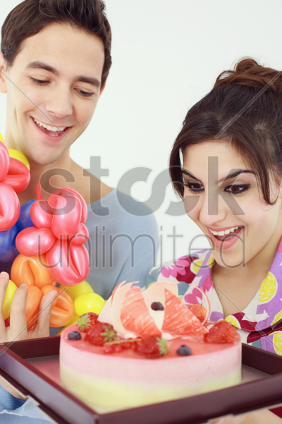 woman holding cake while man holding sculpted balloons stock photo