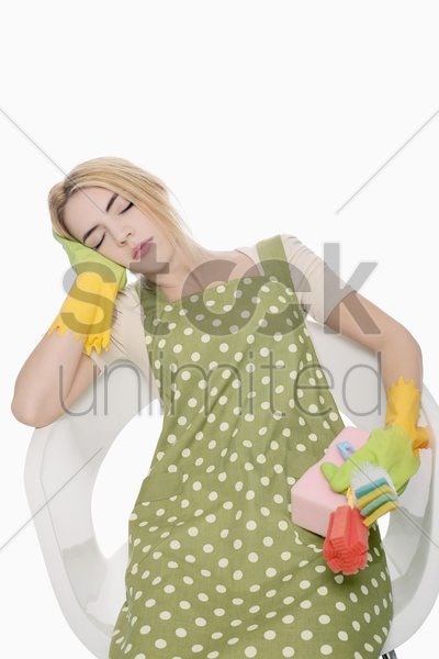 woman holding cleaning products while sleeping on the chair stock photo