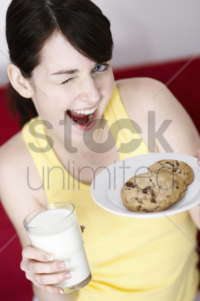 woman holding cookies and a glass of milk stock photo