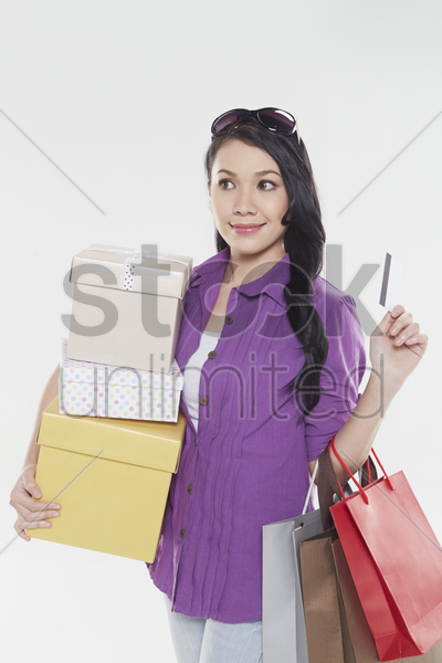 woman holding credit card and shopping items stock photo