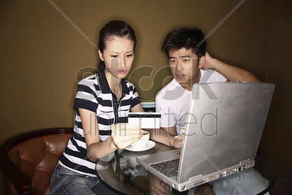 woman holding credit card while using laptop, man scratching head while looking stock photo