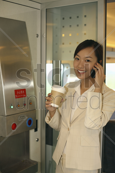 woman holding cup of coffee while talking on the phone stock photo