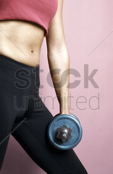 woman holding dumbbell stock photo