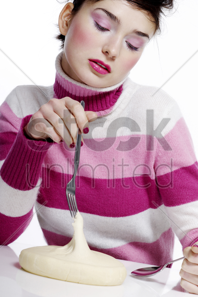 woman holding fork and spoon with dough on the table stock photo