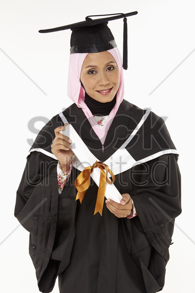 woman holding graduation scroll, smiling stock photo