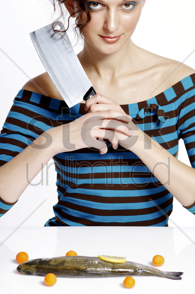 woman holding knife with a fish on the table stock photo