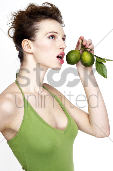 woman holding limes stock photo