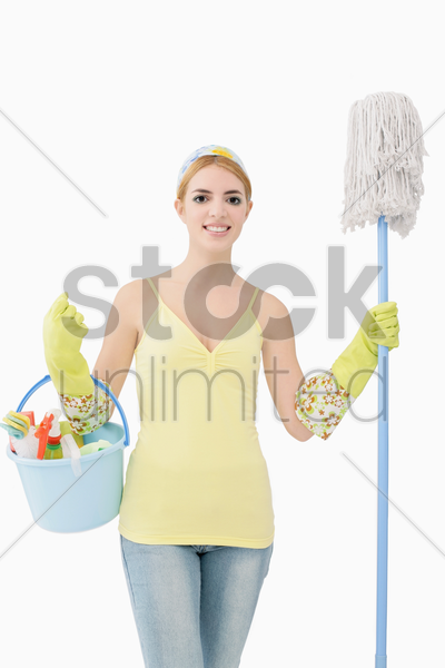 woman holding mop and a pail of cleaning products stock photo