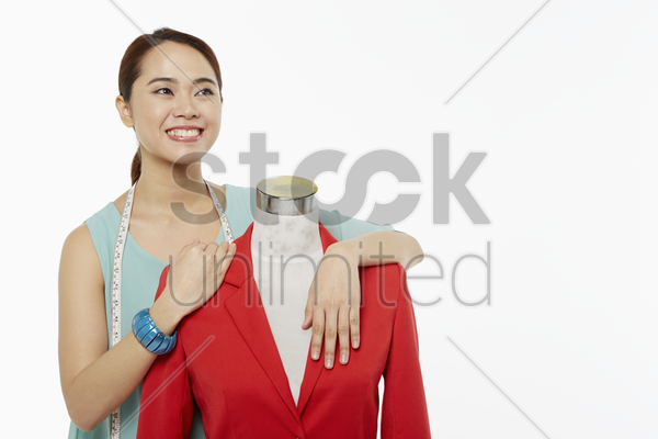 woman holding on to a mannequin, smiling stock photo