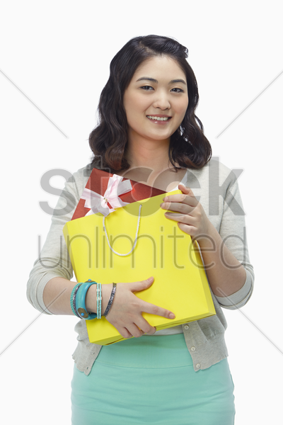 woman holding on to a paper bag with a gift box in it stock photo