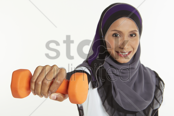 woman holding out a dumbbell stock photo