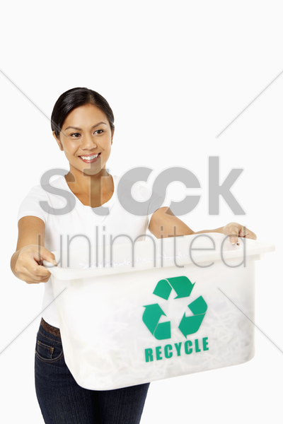 woman holding out a plastic box with a recycle logo on it stock photo