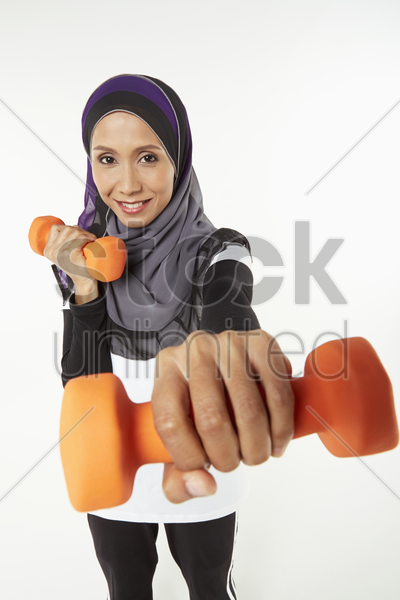 woman holding out dumbbells stock photo
