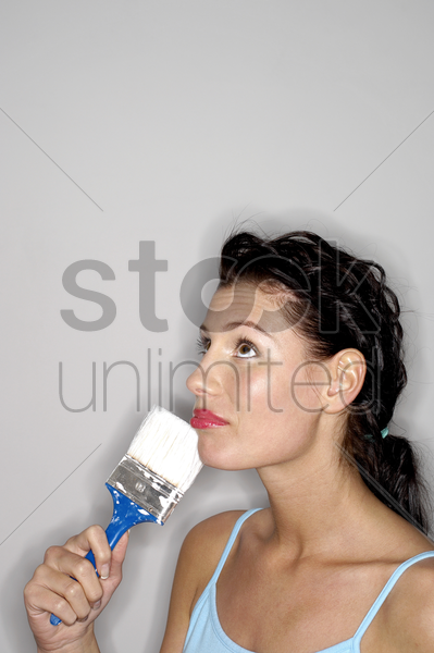 woman holding paint brush thinking stock photo