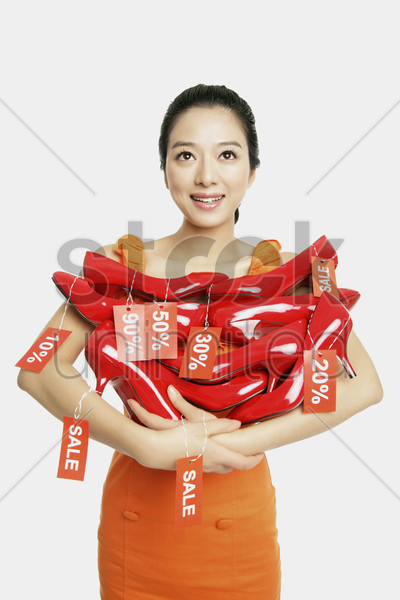 woman holding red stilettos with sale labels stock photo