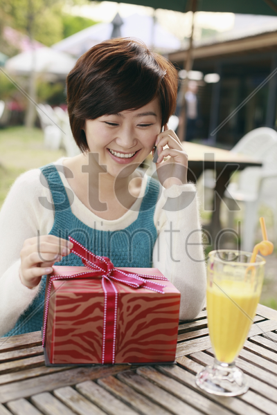 woman holding ribbon at gift box while talking on the phone stock photo