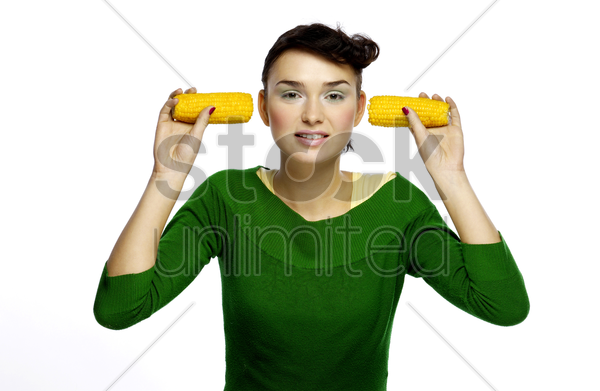 woman holding two ears of corn stock photo
