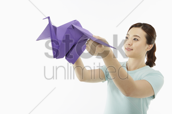 woman holding up a big paper bird stock photo